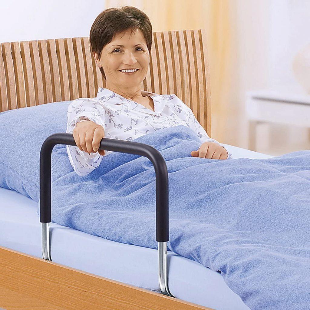 Ältere Dame hät sich an einem Bettgriff fest, der als Aufstehhilfe aus dem Bett dient.